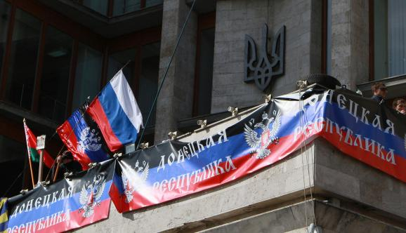 "Flags of the Russian Federation and the ""Donetsk People's Republic"" on a government building in the occupied part of the Donbas"