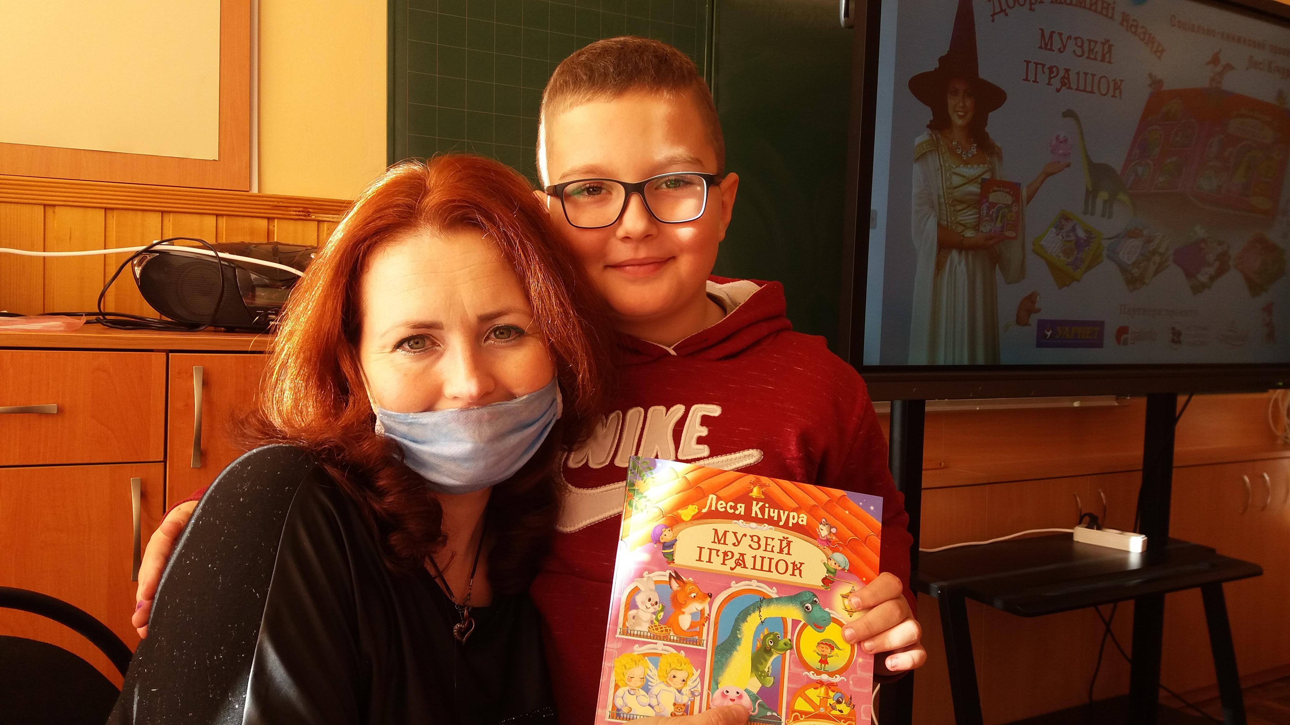 Леся Кічура з дитиною і книгою